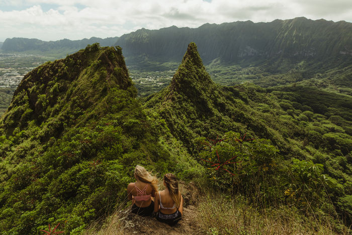 two girls sitting ontop of mountain hawaii