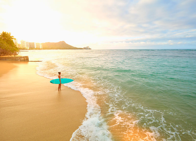 girl on beach with surfboard hawaii