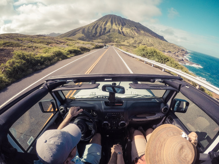couple in open top car driving maui coastline hawaii