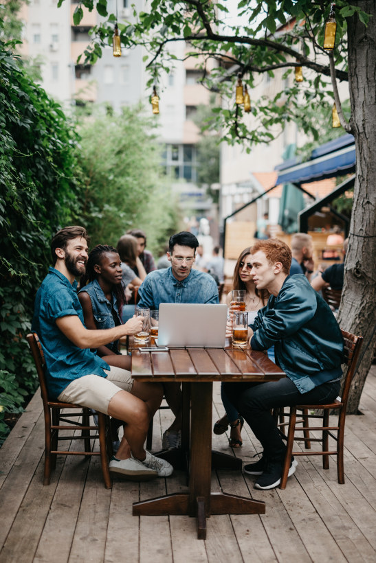 group sitting around laptop at table with beers in europe