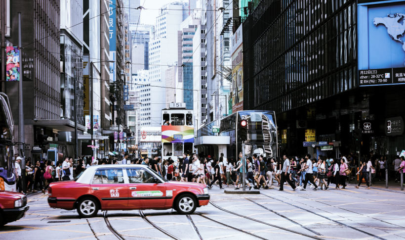 busy hong kong street with taxi in foreground