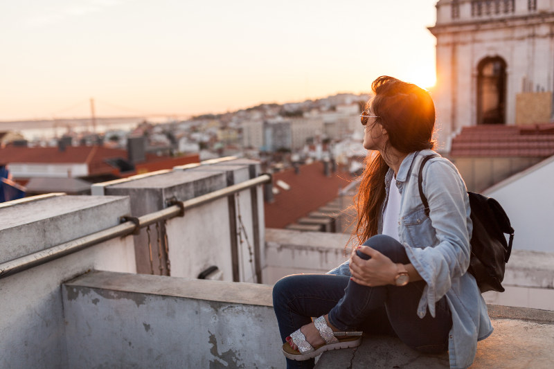 Woman looking out over rooftops in Lisbon, Portugal.