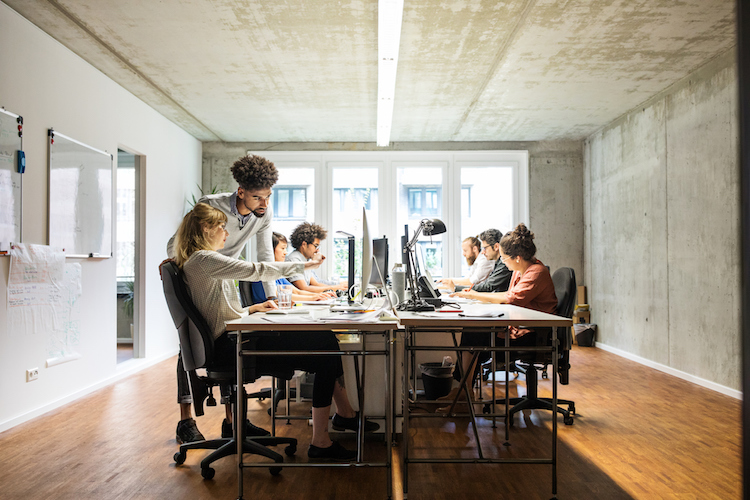 Business people discussing over computer in creative office
