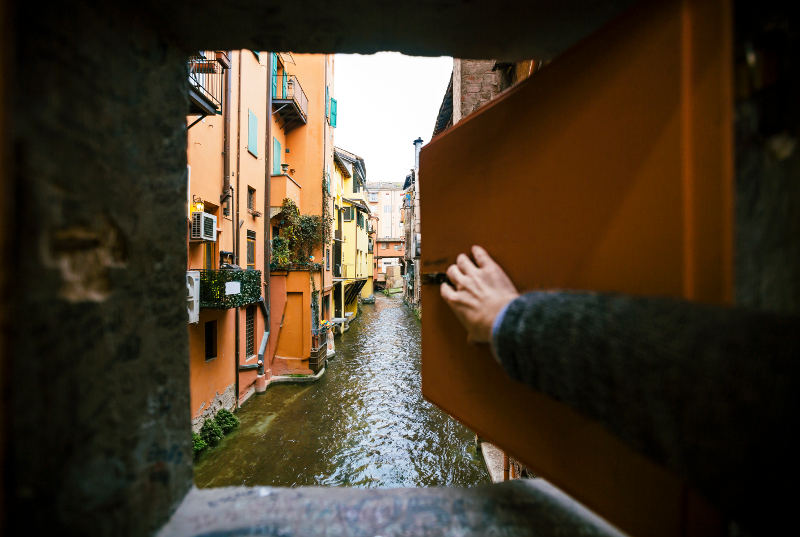 man pushing open window onto canal Bologna italy
