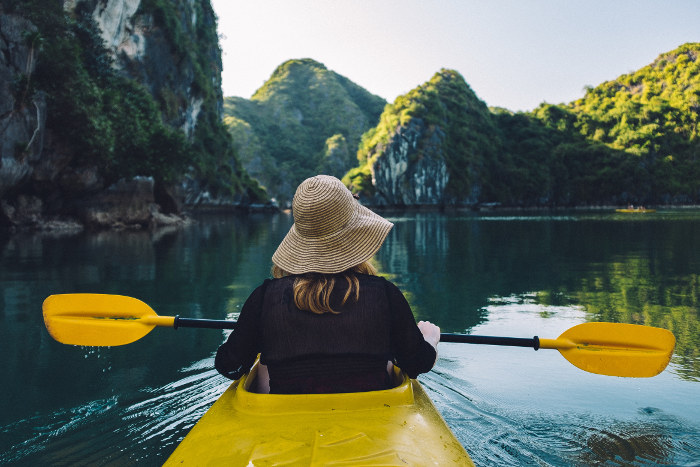 woman kayaking halong bay from behind