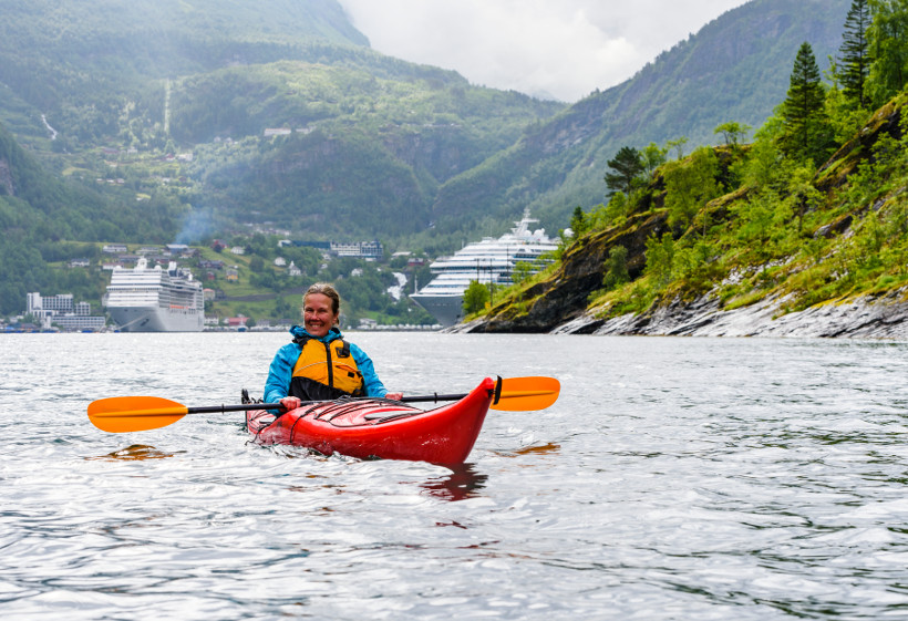 kayaker in fjord with cruise ship in background
