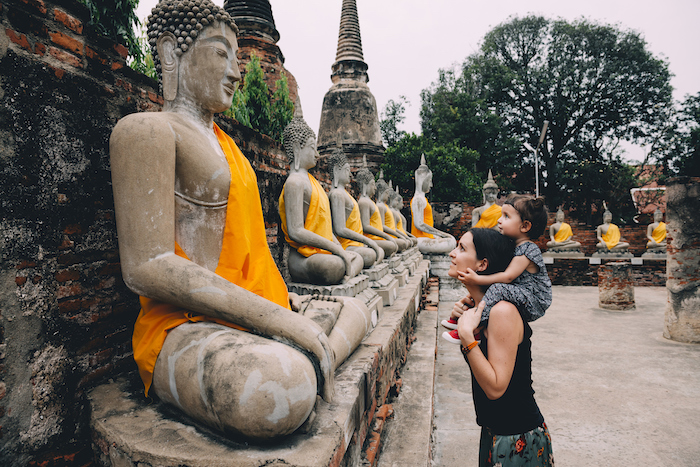 mother and daughter look at row of statues in Wat Yai Chai Mongkhon