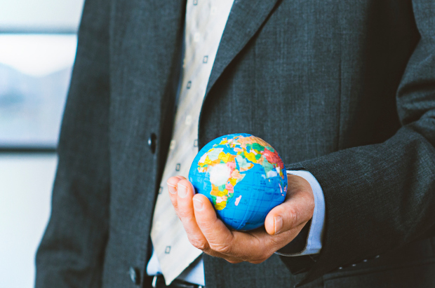 A business man holding a globe in his hand