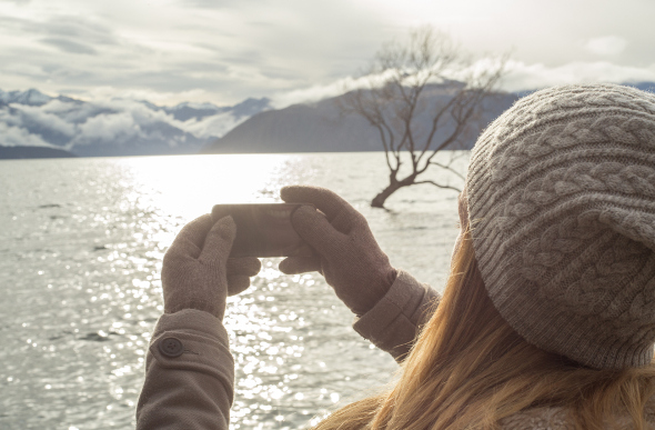 A girl taking photos wearing gloves and a hat