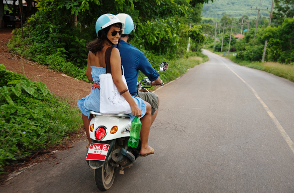 A couple riding a motor scooter through the jungle