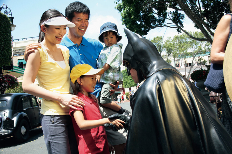 Batman character shakes hand of child with family at Movieworld on the Gold Coast.