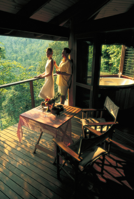 A couple enjoy the views from their balcony at Mount Quincan Crater Retreat in North Queensland.