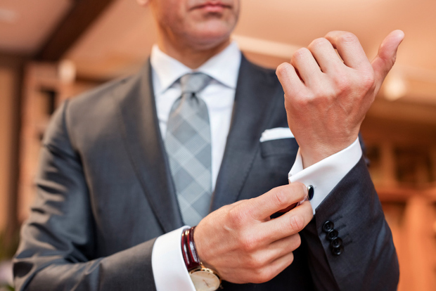 Well dressed business man adjusts cuff links