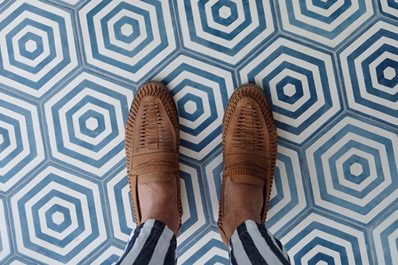 A man's feet against tiles at Halcyon House, NSW
