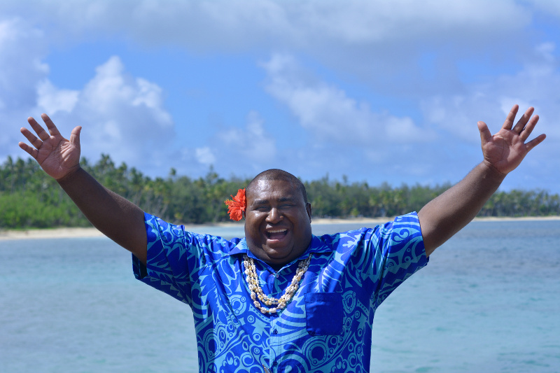 A smiling Fijian holds out his arms in front of the beach.