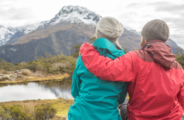 Two people looking at the mountain while wearing hats