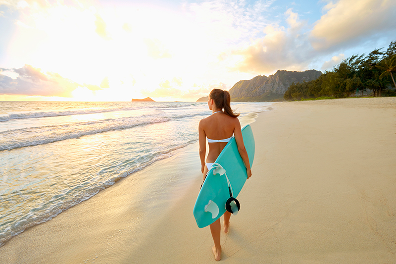 Woman carrying surfboard on Hawaii beach