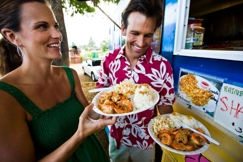 man and woman holding plates of prawns and rice in front of food truck honolulu