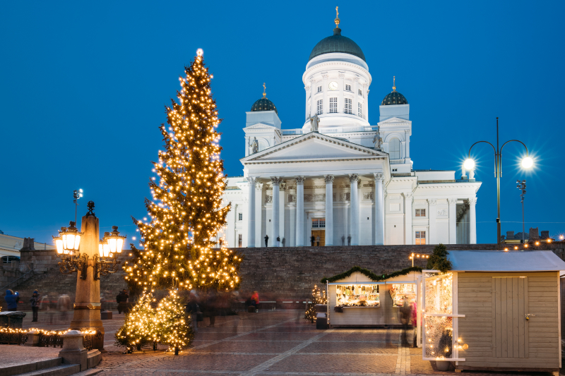 The Helsinki Cathedral in lit up at night, a few stalls below