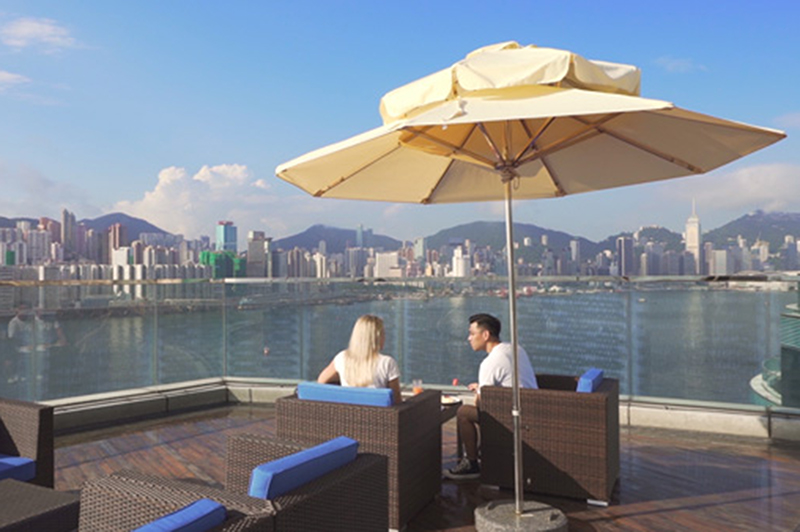 A man and a woman sit by the pool at a Hong Kong hotel.