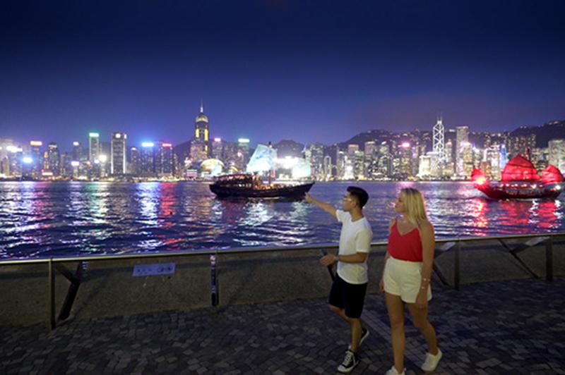 Two people walk along Tsim Sha Tsui Promenade in Kowloon, Hong Kong.