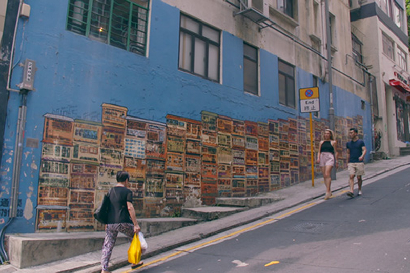 People walk past vibrant street art in Old Town Central, Hong Kong.