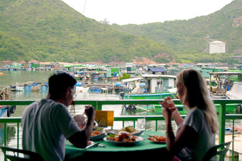 Two people eat a seafood lunch on a floating restaurant on Lamma Island, Hong Kong.