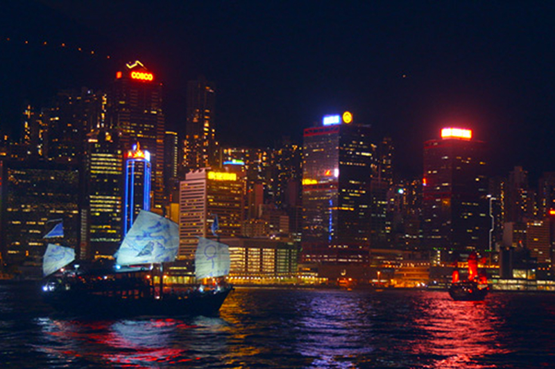 A junk boat cruises Hong Kong's Victoria Harbour amid the sparkling night-time lights.
