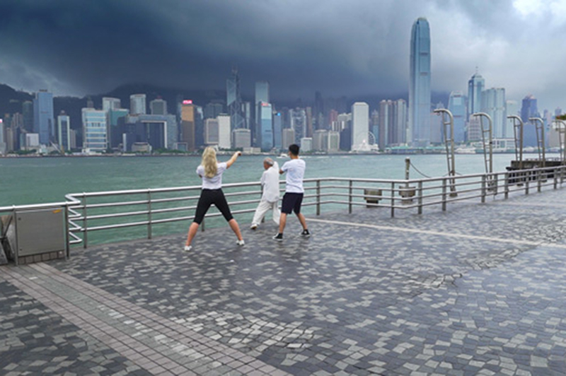 Three people practise tai chi by the harbour in Hong Kong.