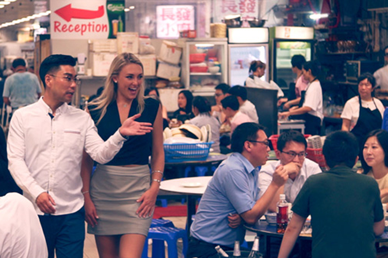 Two people walk through the bustling Tung Po food court in Hong Kong.