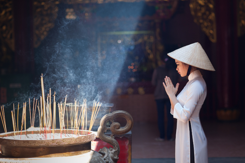 Local woman at temple with incense in Ho Chi Minh City, Vietnam.