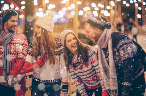 A group of friends laughing in Christmas sweaters