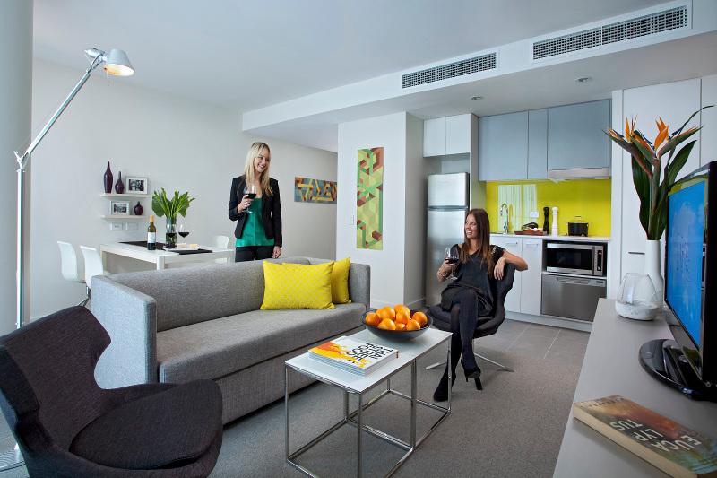 Two women relax with a glass of wine in an apartment at the Citadines on Bourke hotel in Melbourne, Victoria.