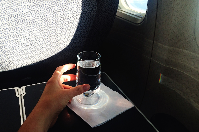 A glass of water on an airplane tray table