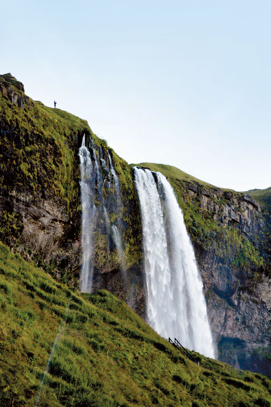 man at top of waterfall iceland