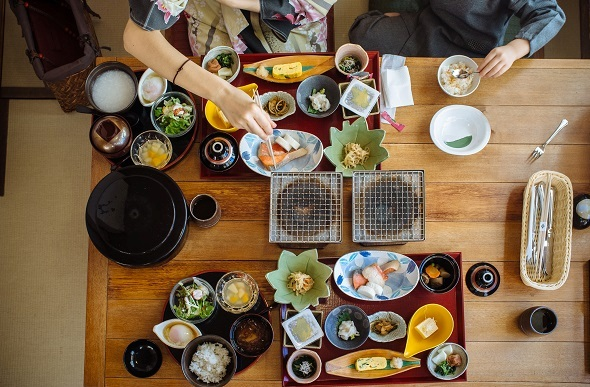 two people eating japanese food from above