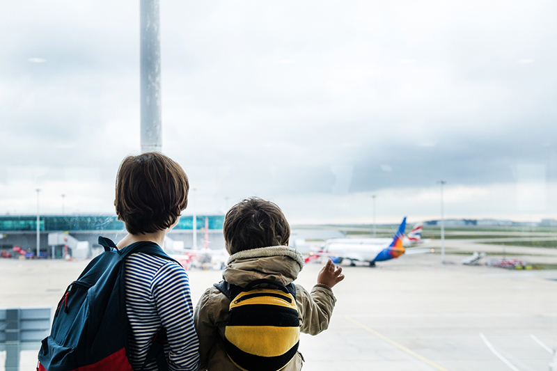 two boys watch planes at the airport