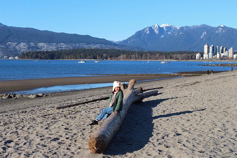 Girl sits on log at Kitsilano Beach, Vancouver