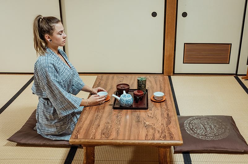 A woman sits within a Japanese temple stay room