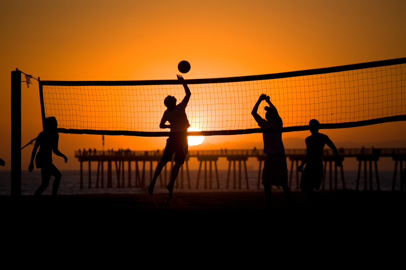 People play volleyball at sunset at LA's Hermosa Beach.