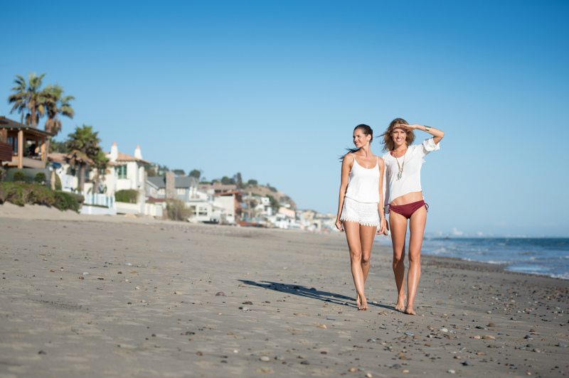 Two women stroll past mansions at Malibu Beach, Los Angeles.