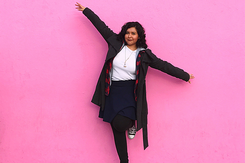 A young woman poses in front of the pink wall on Los Angeles' Melrose Avenue