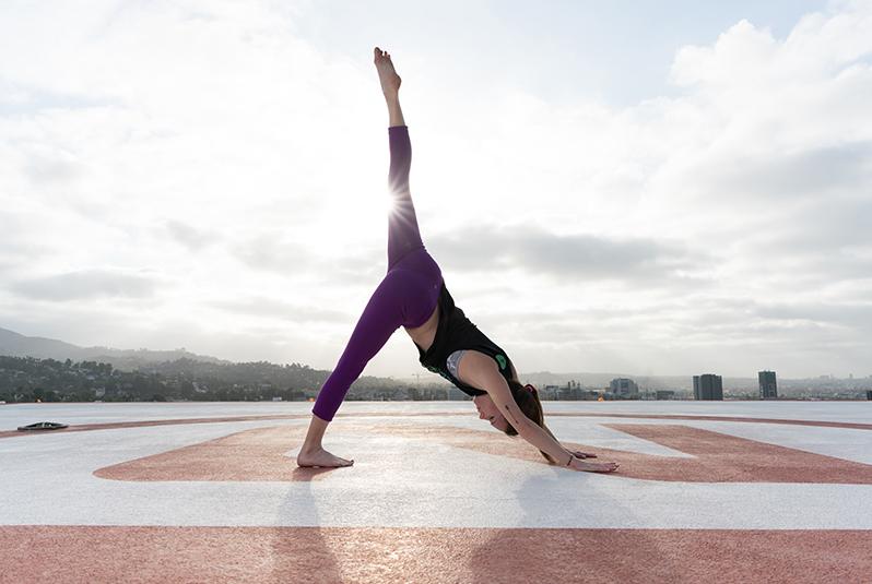 Women doing yoga pose on a helipad in LA