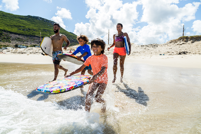 family running into surf - life lessons from travelling with kids