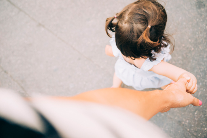 woman holding her toddlers hand while walking - life lessons from travelling with kids