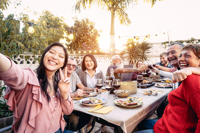 a group of people enjoying a meal together outdoors - lessons from travelling with kids