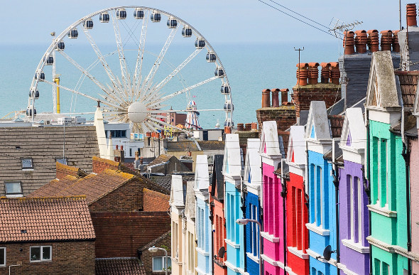 Colourful buildings in Brighton, England, with a ferris wheel and the sea in the background.