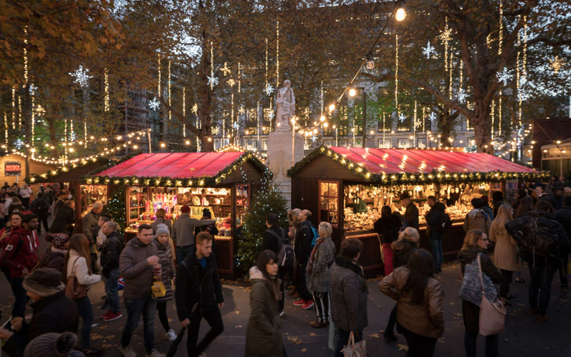 Busy markets of Christmas in Leicester Square. Fairy lights hang from a statue and the trees