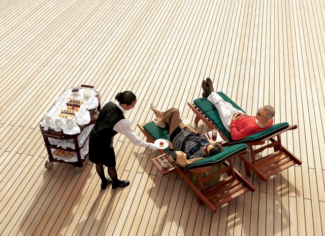 Couple being served champagne on cruise deck