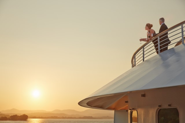 Couple standing on deck of luxury cruise in black tie